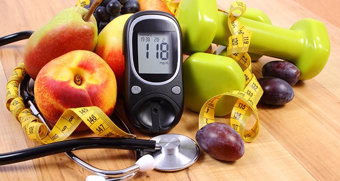 Glucose meter in the midst of peach, pear, grapes, stethoscope, tape measure, and handweights