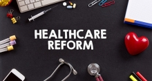 "The words ""healthcare reform"" in the middle of stethoscope, computer keyboard, pens, paperclips, and hypodermic needle"