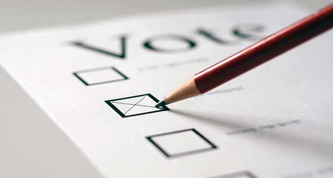 Pencil being used to mark boxes on a voting ballot