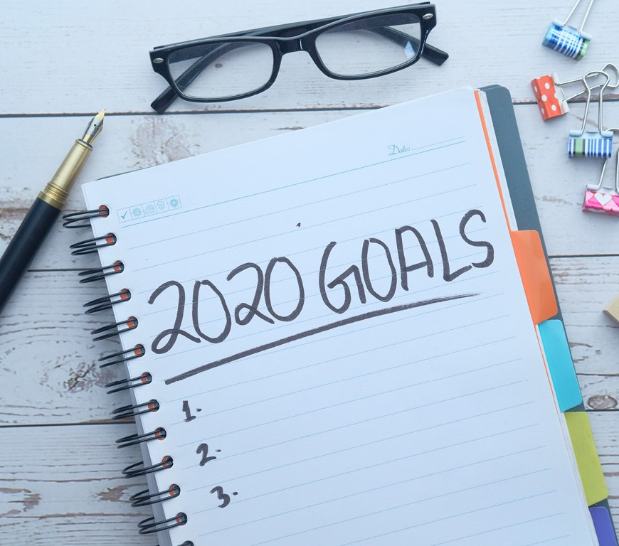 desktop with a notebook where 2020 goals has been written, also on desk: glasses, pen, binder clips